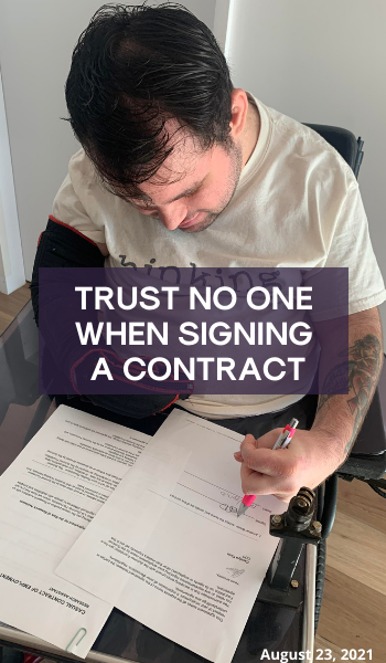 Blog: Trust no one when signing a contract. Image description: Jono in his wheelchair signing a contract. He is wearing a white top that says 'thinking'.