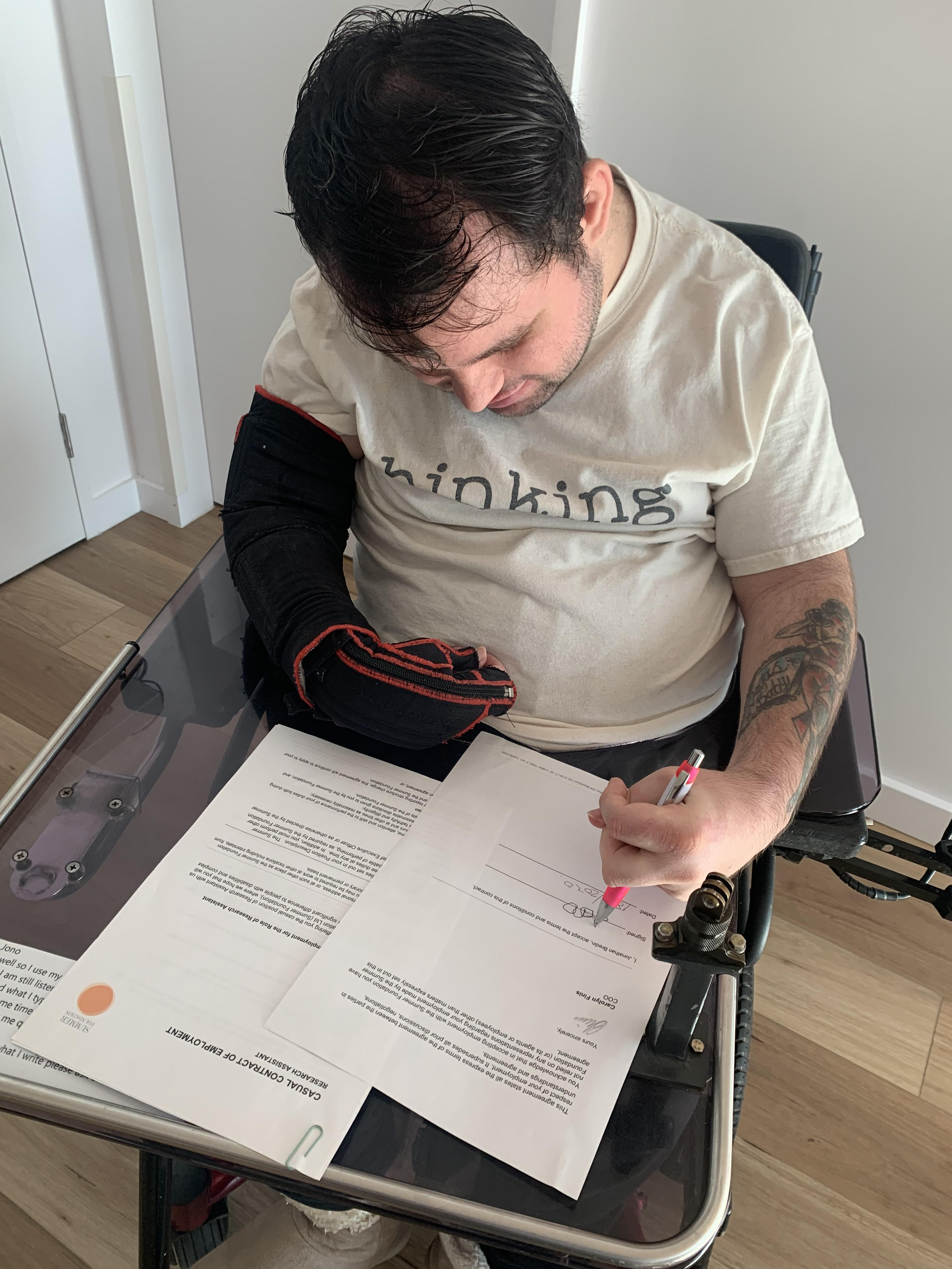Image description: Jono in his wheelchair signing a contract. He is wearing a white top that says 'thinking'.
