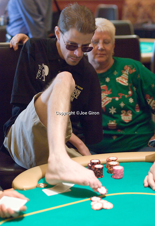 Image of a man playing poker, using his feet to move the chips. The man is wearing sunglasses, a black t-shirt and beige shorts.