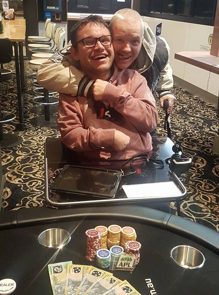 Image of Jono and his friend Jacko. Jono is sitting in his wheelchair, wearing his prescription glass and a light red hoodie. Jacko is standing behind Jono leaning over to hug him, wearing a grey and white jacket.
