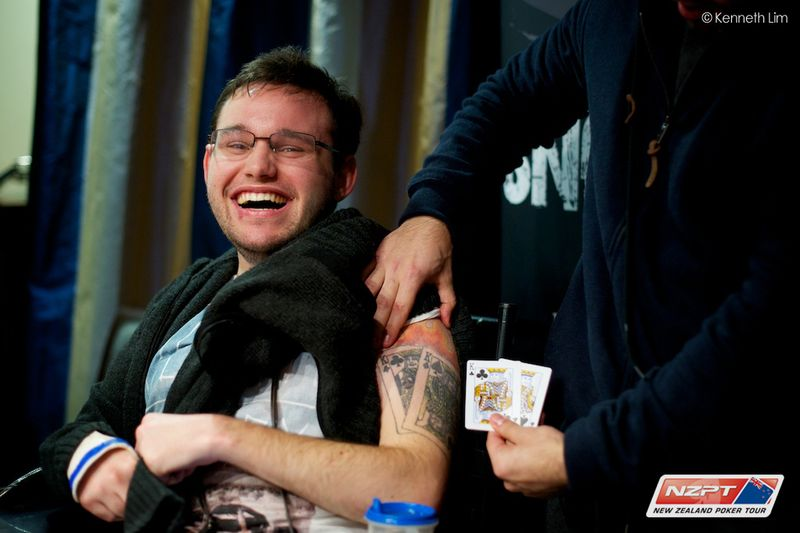 Image description: Jono smiling at the camera, revealing his tattoo on his left arm of two cards showing a pair of black kings, besides two actual cards showing black kings, which he used to win his poker game..
