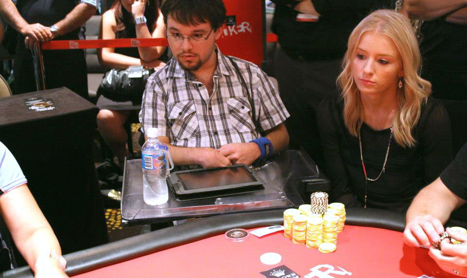 Image desription: Jono sitting at a poker table watching and playing the game. Jono is sitting in his wheelchair, wearing a black and white plaid t-shirt and a pair of prescription glasses. In front of him is a stack of poker chips on a red poker table.