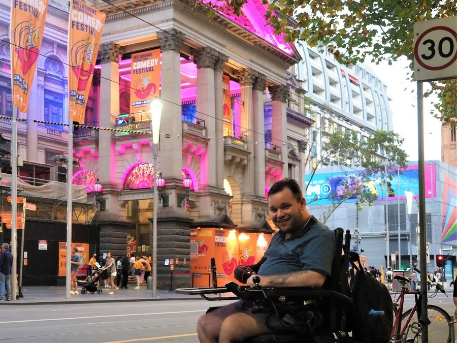 Image description: Jono in Melbourne City. The Melbourne Town Hall is lit up behind him and decorated with signs for Melbourne Comedy Festival.