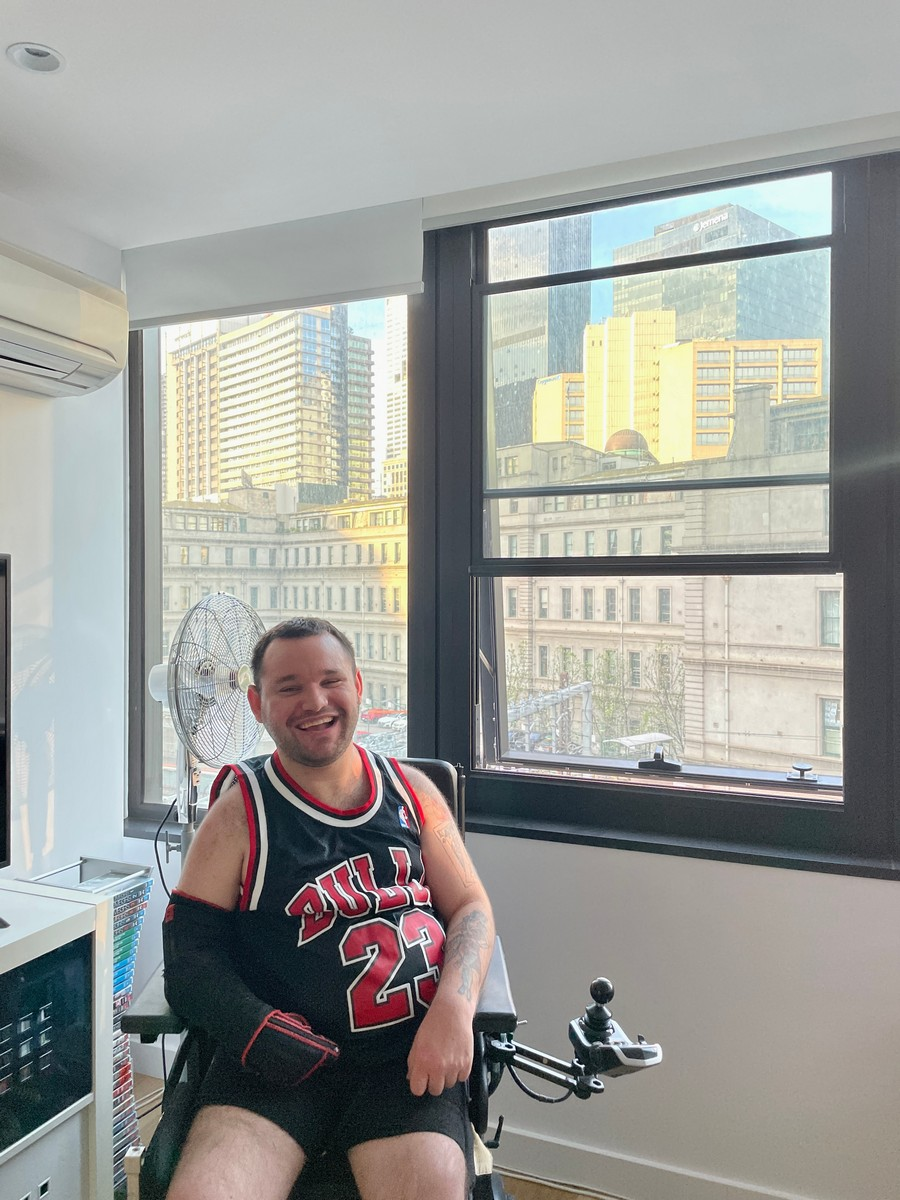 Image description: Jono in his living room. Afternoon light is coming through the window behind him which has views of the city.