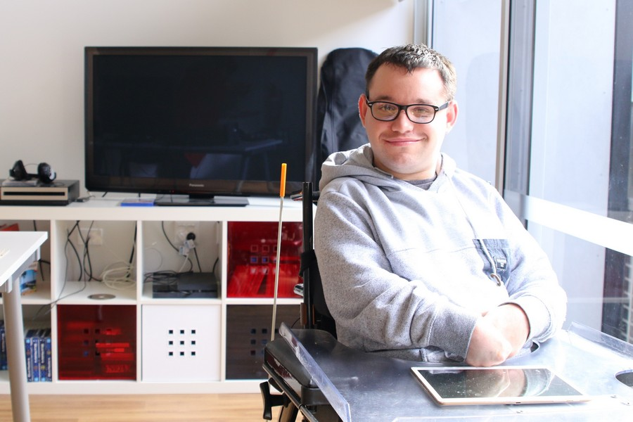 Image description: Jono in his Frankston apartment living room, in front of a TV and cabinet.