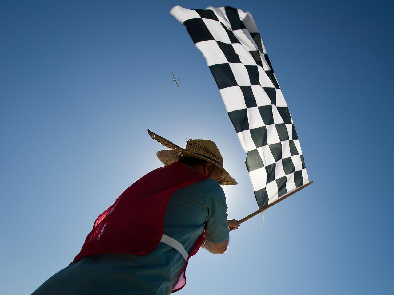 Eine Person schwenkt eine Zielflagge mit Schachbrettmuster