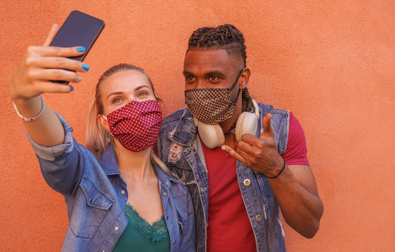 Multi racial couple taking a selfie with face masks on.