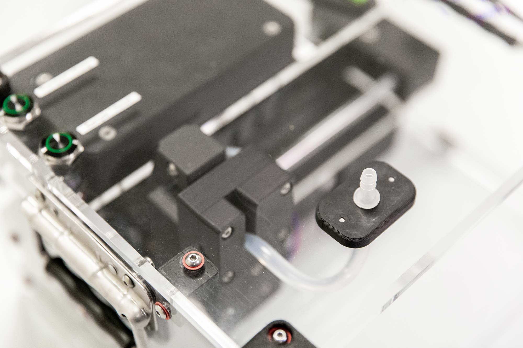 Photo of Syp autosampler device on a benchtop in the lab. Closeup on barbed inlet.