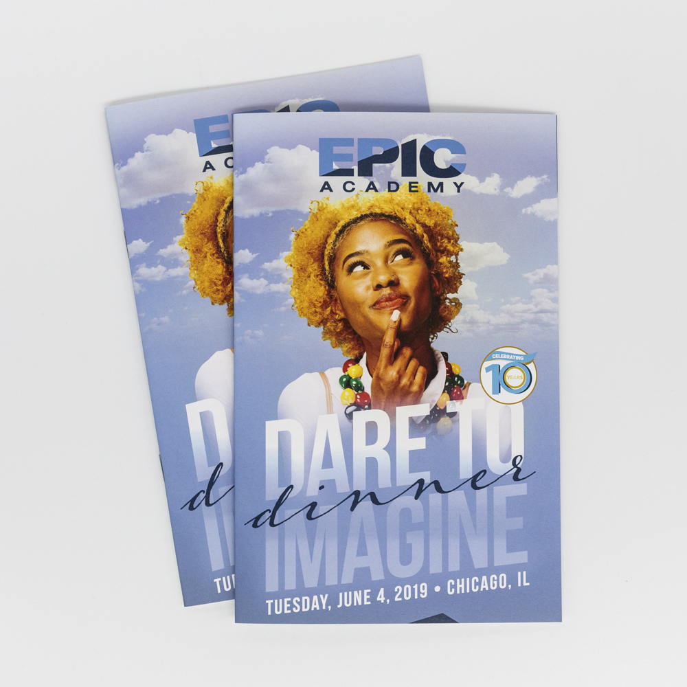 """Image of a booklet for an event titled """"Dare to Imagine"""" with a photo of a girl in the clouds."""