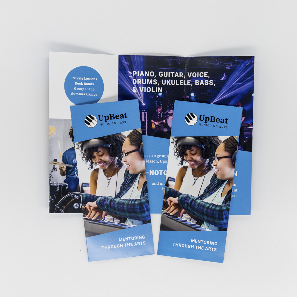 Image of trifold brochure for Upbeat Music and Arts featuring a photo of kids playing a keyboard.