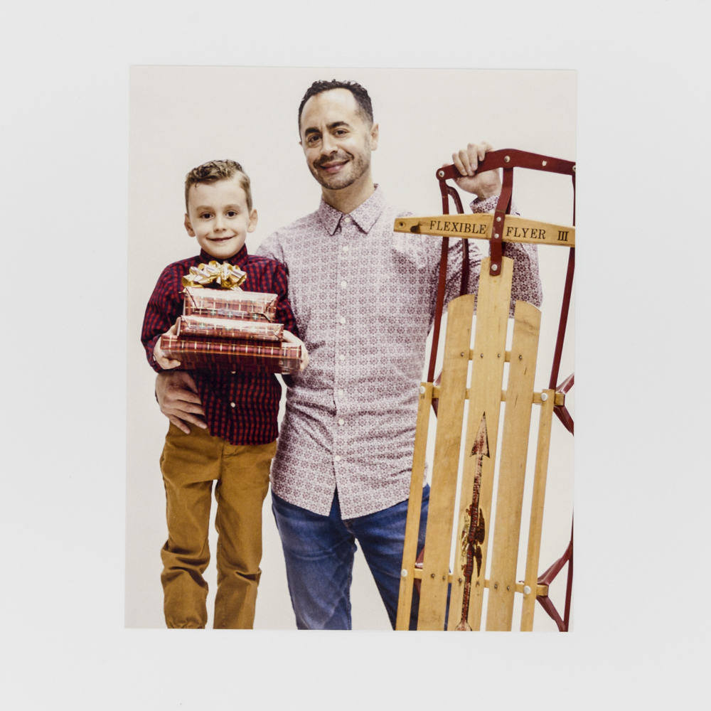 Photo of a father and his son with a sled.