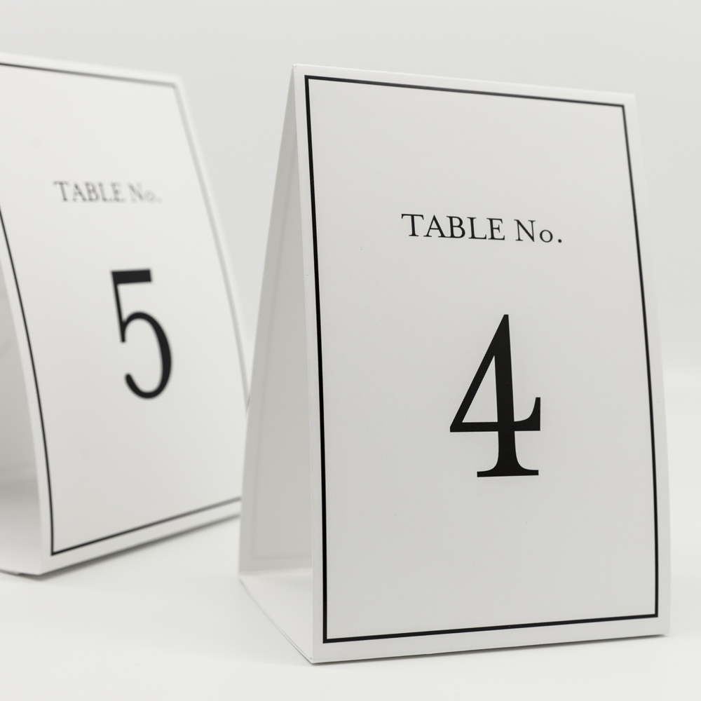 """Two place cards, one in front with text """"Table no. 4"""" and behind it with the text """"Table no. 5""""."""