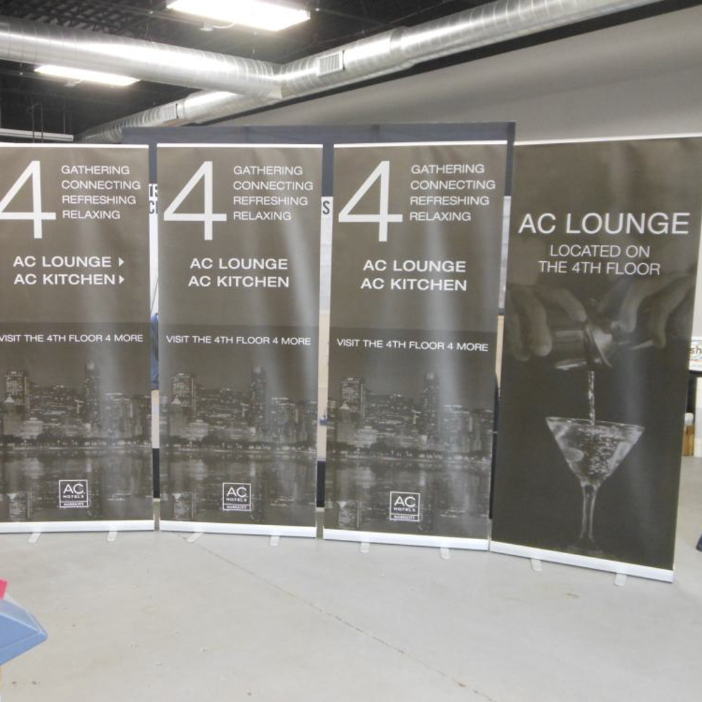 4 retail signage banners on stands in a lounge.
