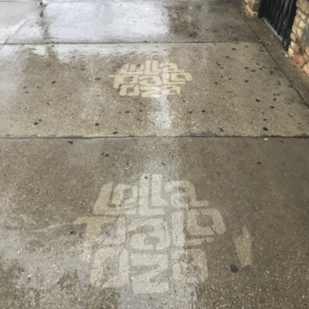 Two Lollapalooza reverse graffiti stencilings on sidewalk