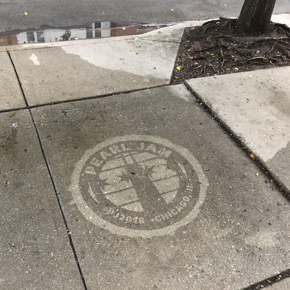Pearl Jam reverse graffiti stenciling on sidewalk near a tree.