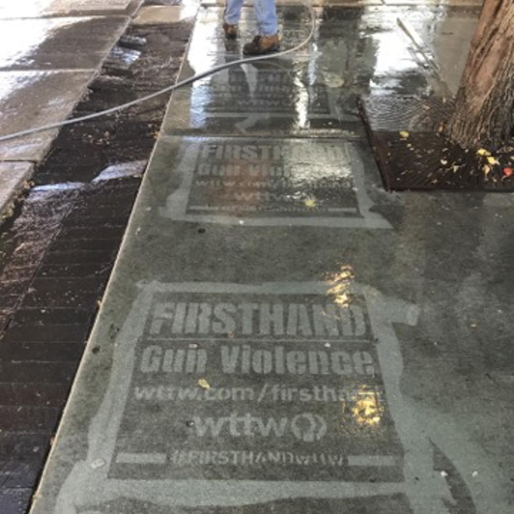 WTTW firsthand gun violence reverse graffiti stenciling on sidewalk near tree.