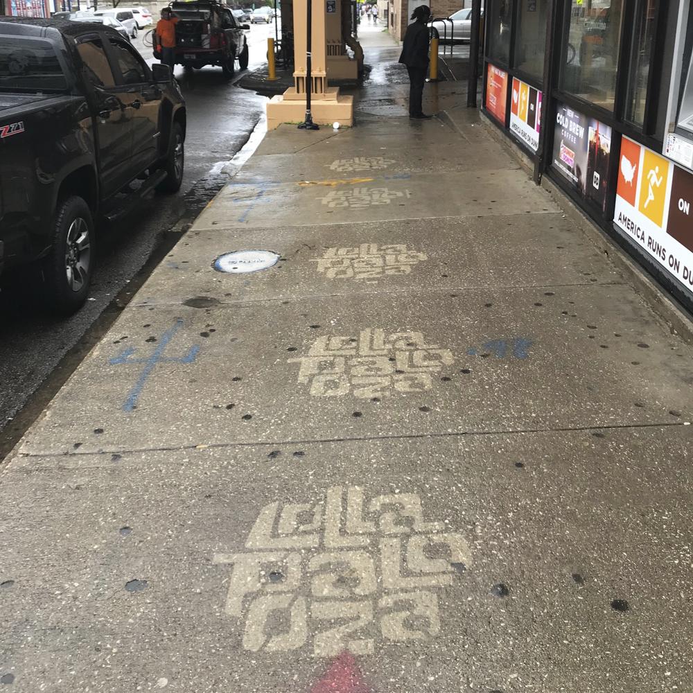 Lollapalooza reverse graffiti stenciling on sidewalk near store windows.