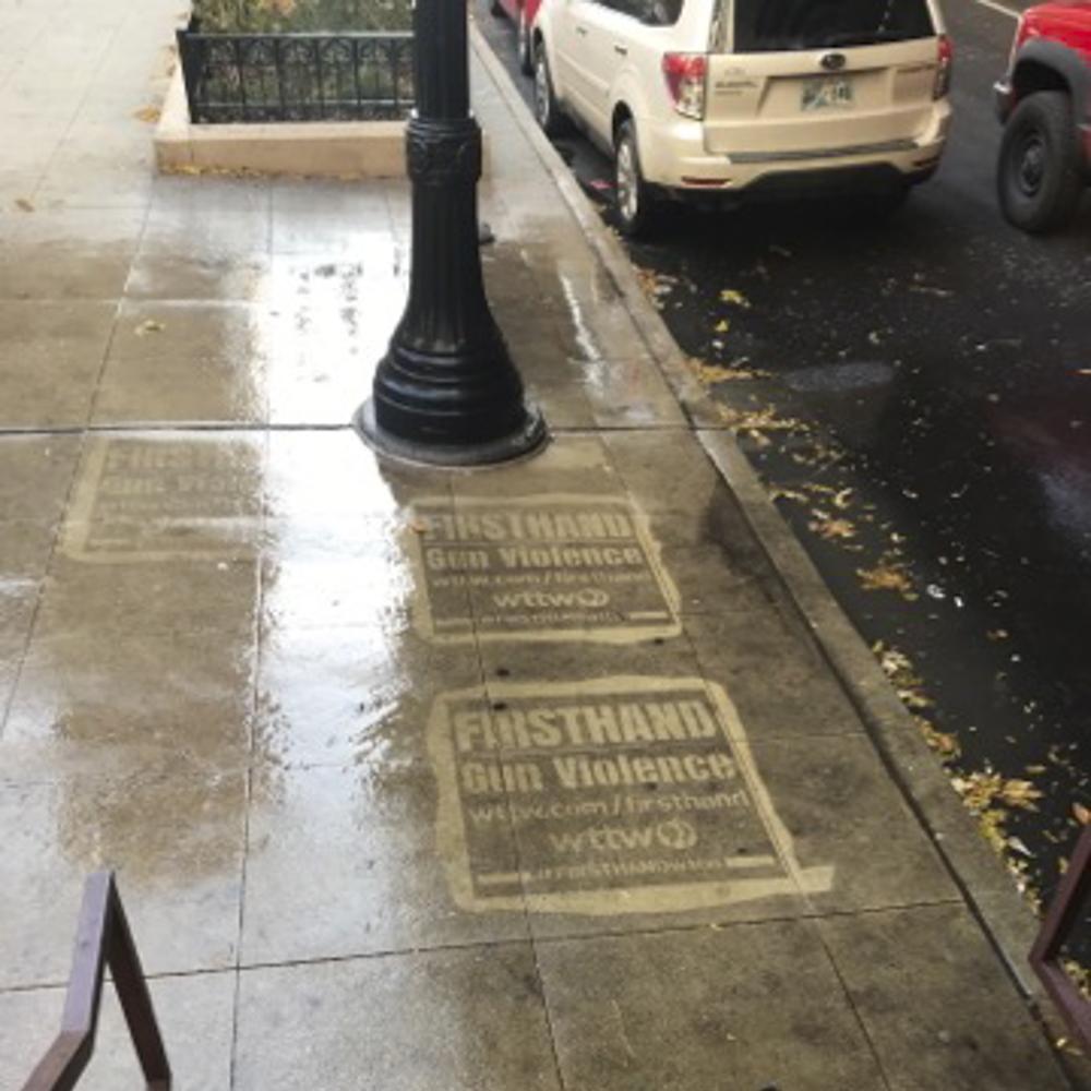 WTTW firsthand gun violence reverse graffiti stenciling on sidewalk near light post.