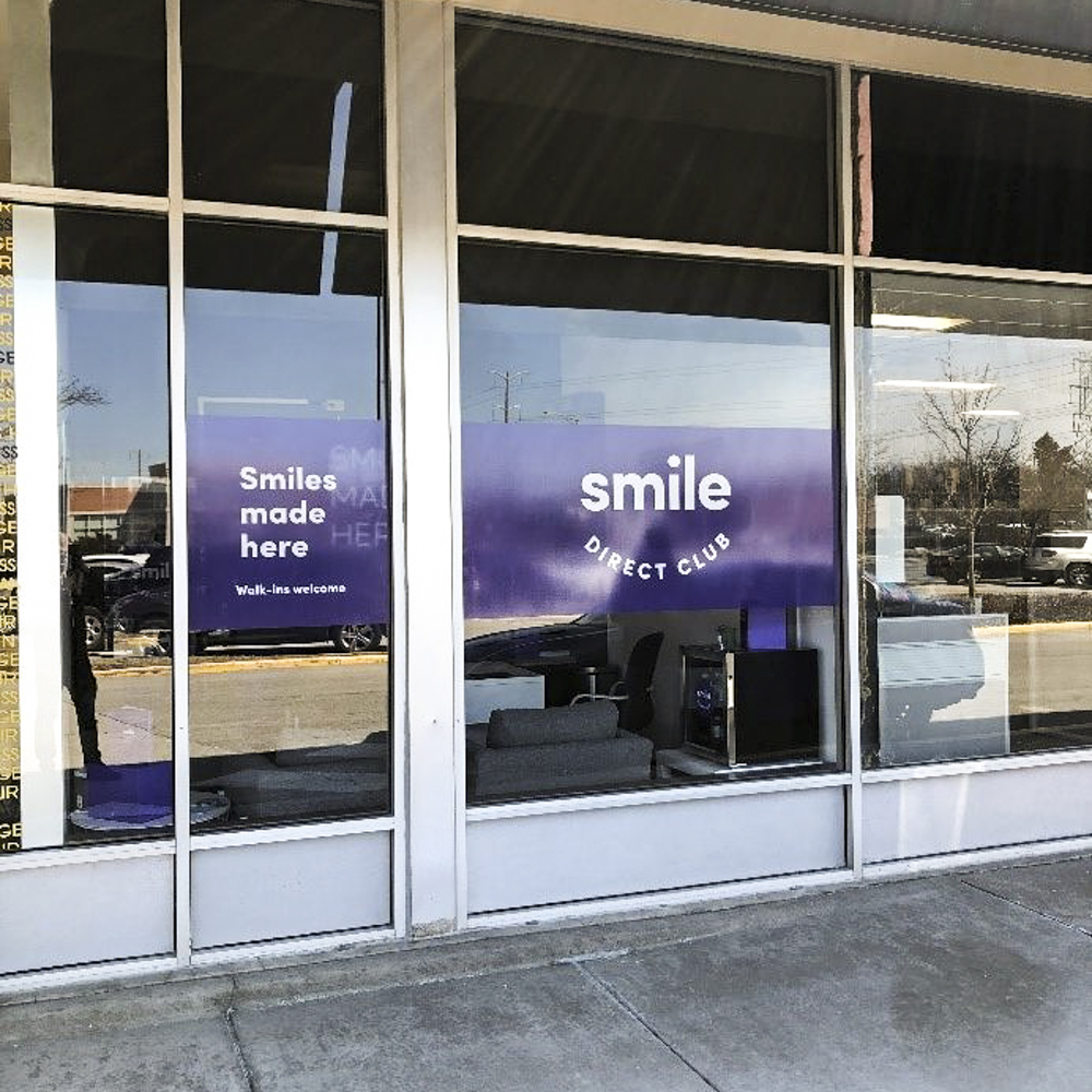 """Purple window cling with work """"smile""""."""