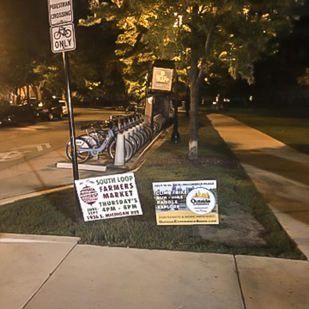 Two yard signs displayed near bike rack.