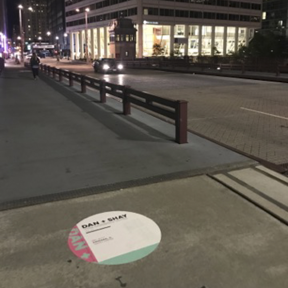 """Photo of round floor graphic with """"Dan & Shay"""" text on city sidewalk."""