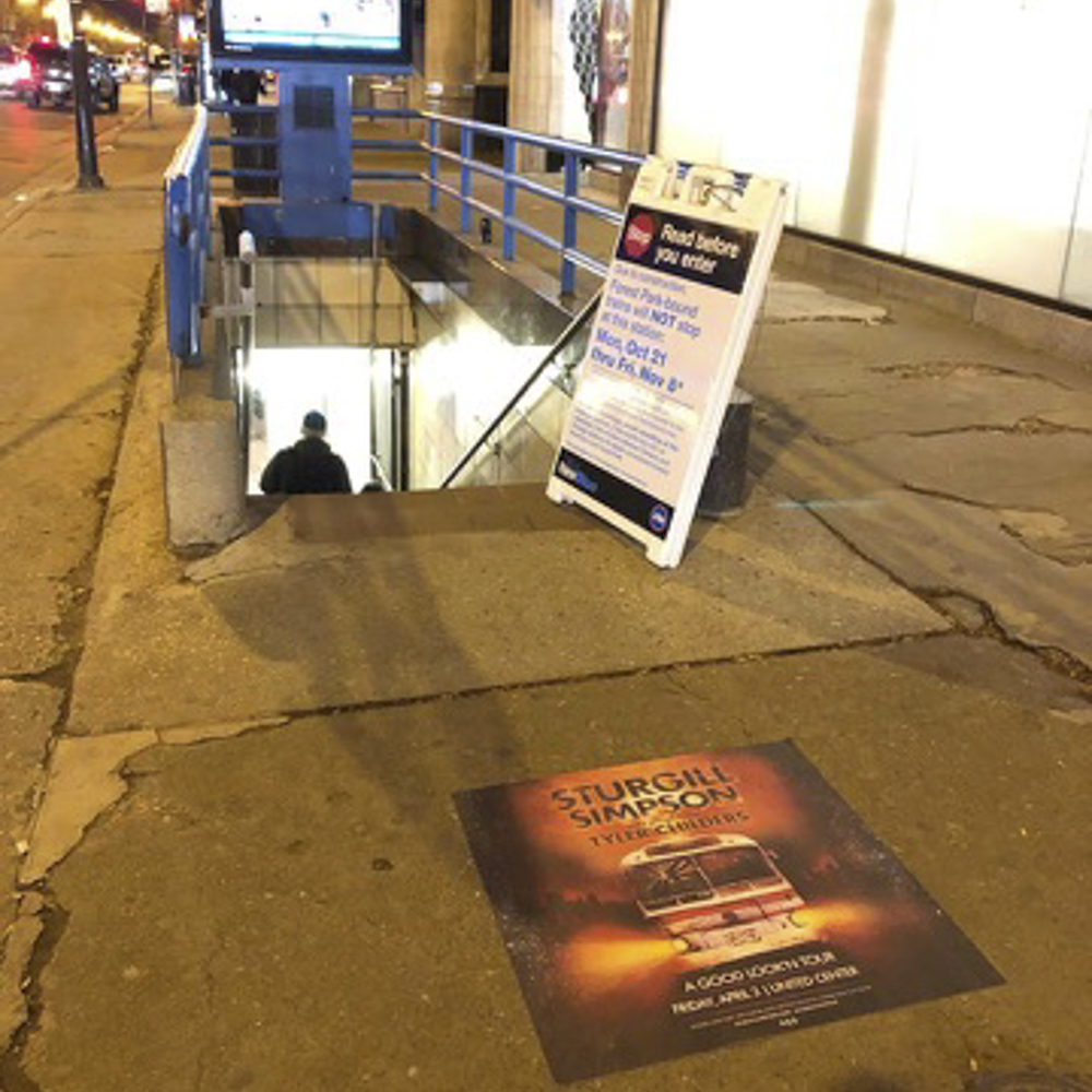 Photo of Sturgill Simpson floor graphic with image of a bus with lights on, on sidewalk in front of subway stop.
