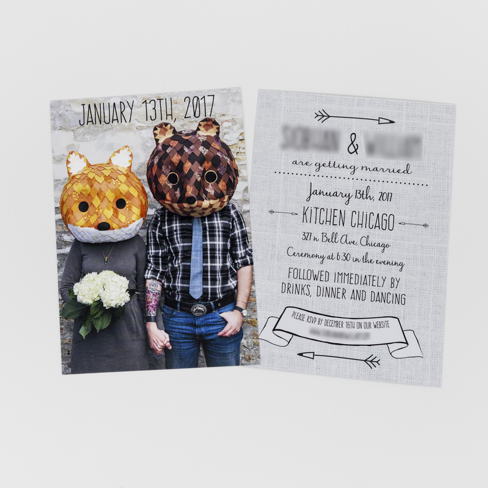 Wedding invitation featuring an image of a man and women wearing novelty head coverings.