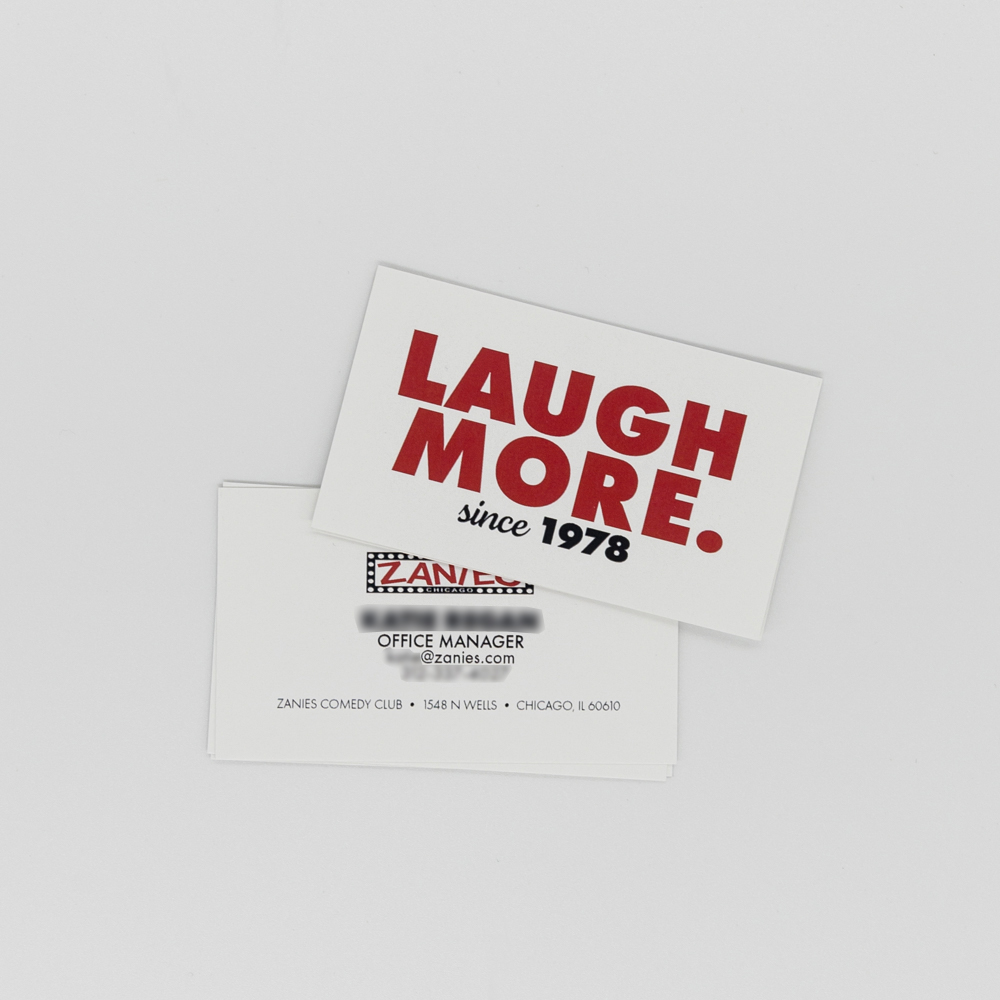 """Image of business card for Zanies comedy club with """"Laugh More"""" Text."""