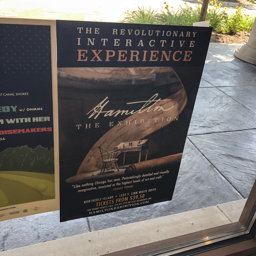 Image of a poster for an interactive exhibit in the window of a retail business.