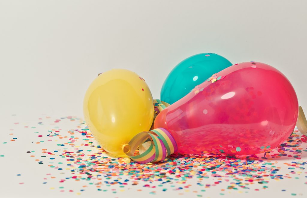 Colourful balloons on the ground in confetti.