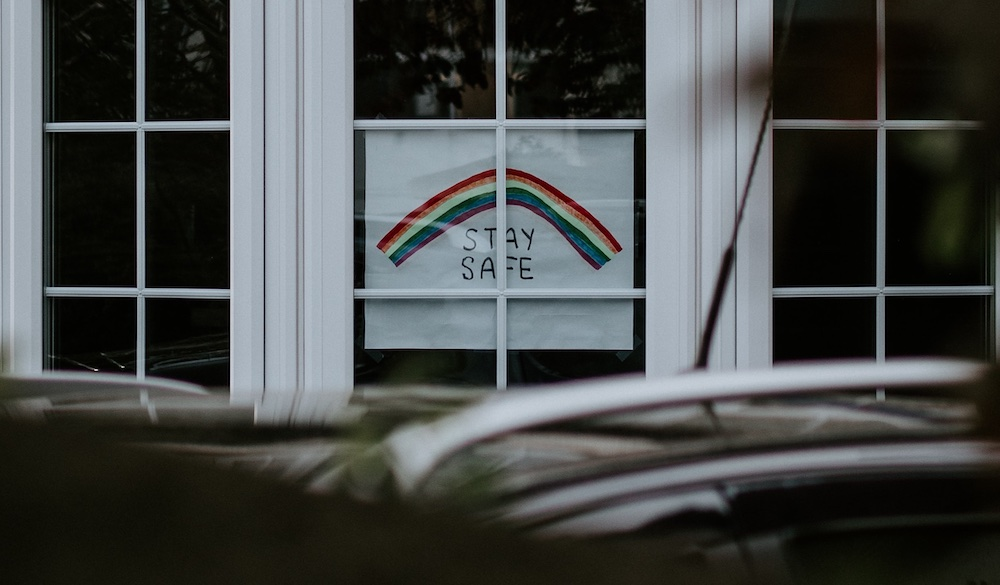 """Child drawing of a rainbow in a window with a sign to """"stay safe"""""""
