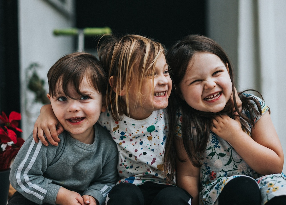 Three young children smiling and hugging each other.