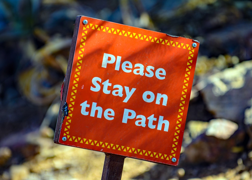 Red sign urging to stay on the path