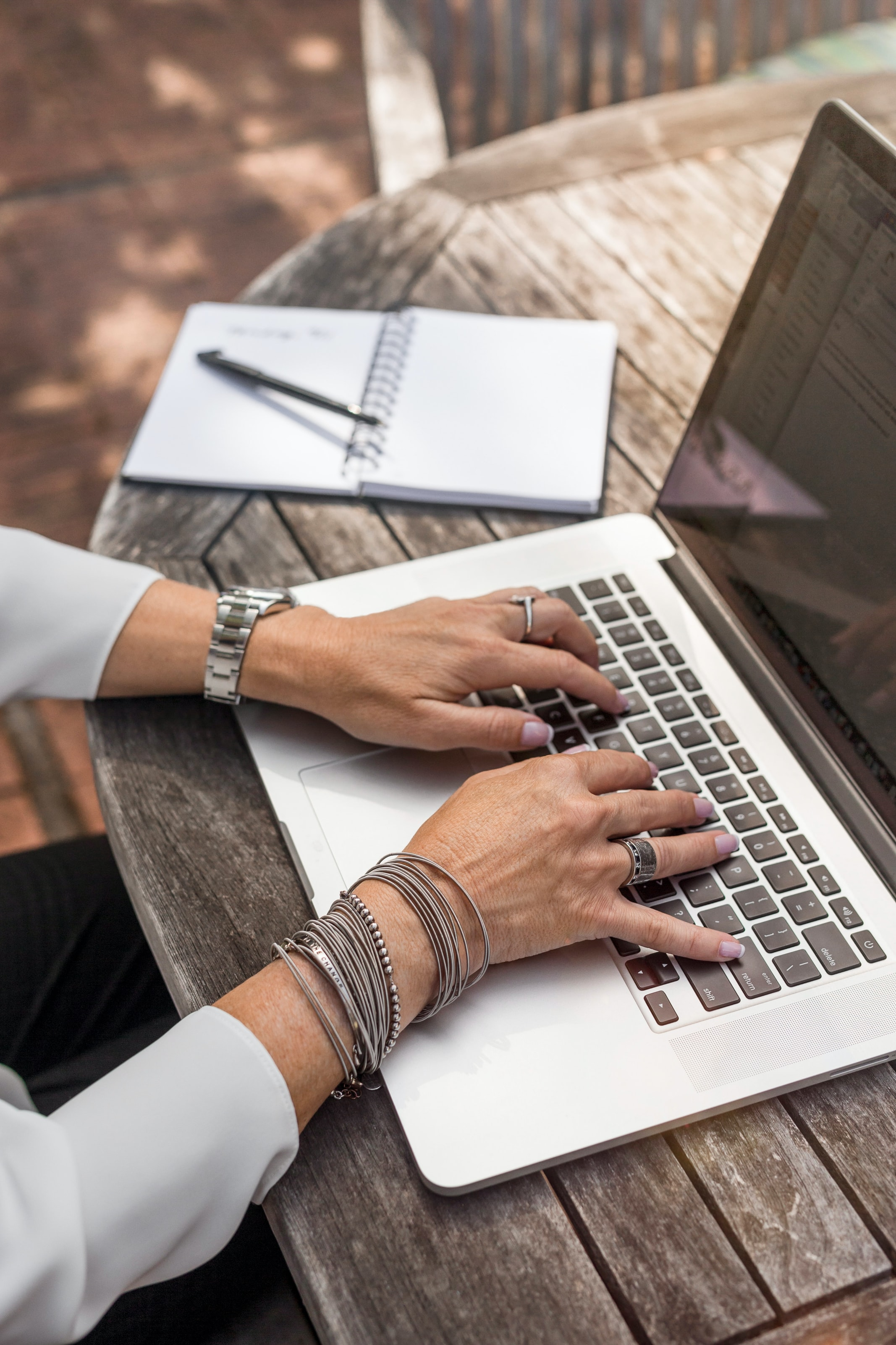 The hands of a person typing on a laptop with a notebook and a pen next to the laptop