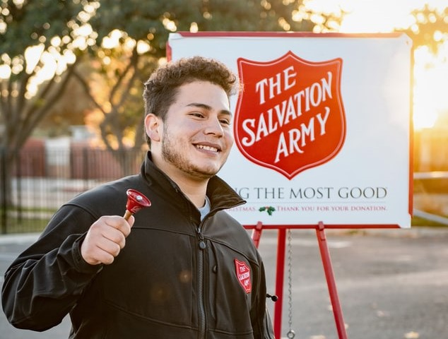 A man ringing a red bell, wearing a The Salvation Army jacket with a The Salvation Army poster behind him. The logo is the same red colour as the bell.