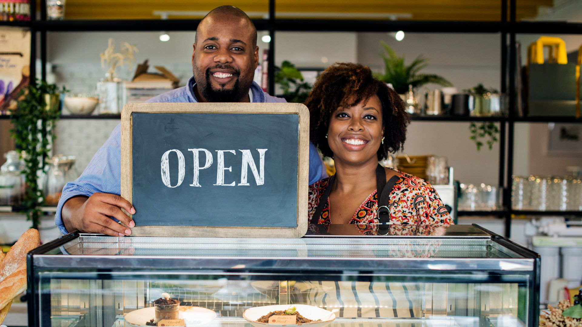 """Small business owner couple holds """"open"""" sign"""
