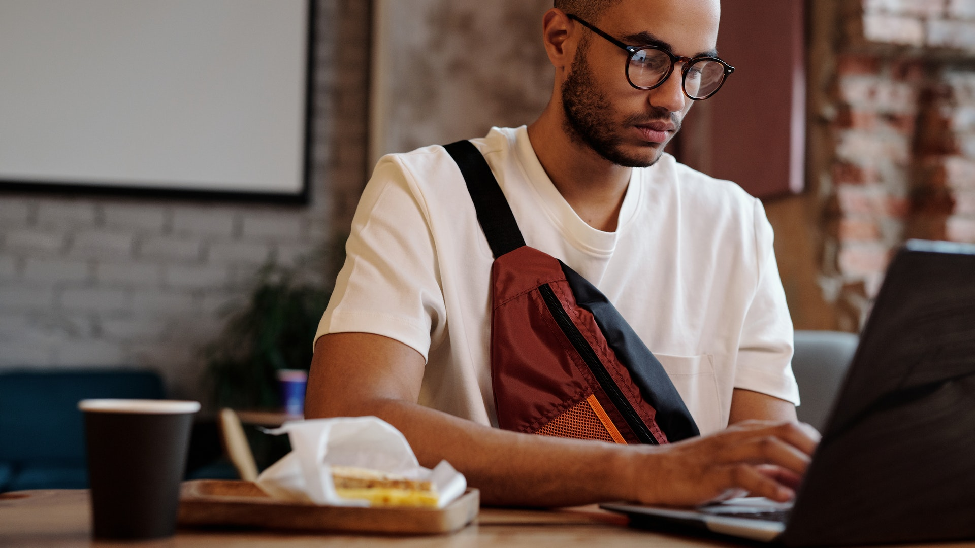 Young hipster male typing on computer