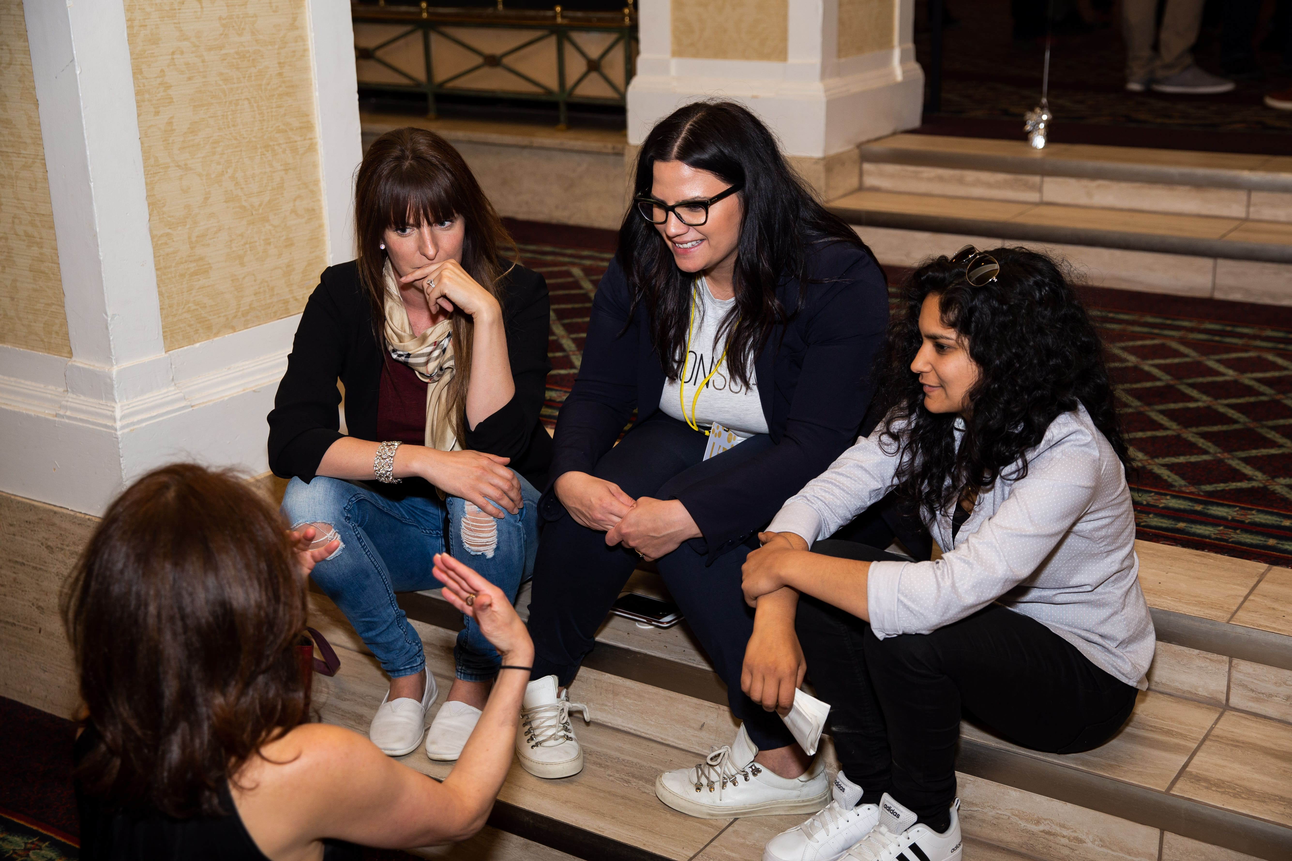4 women sitting on 2 couches and talking.
