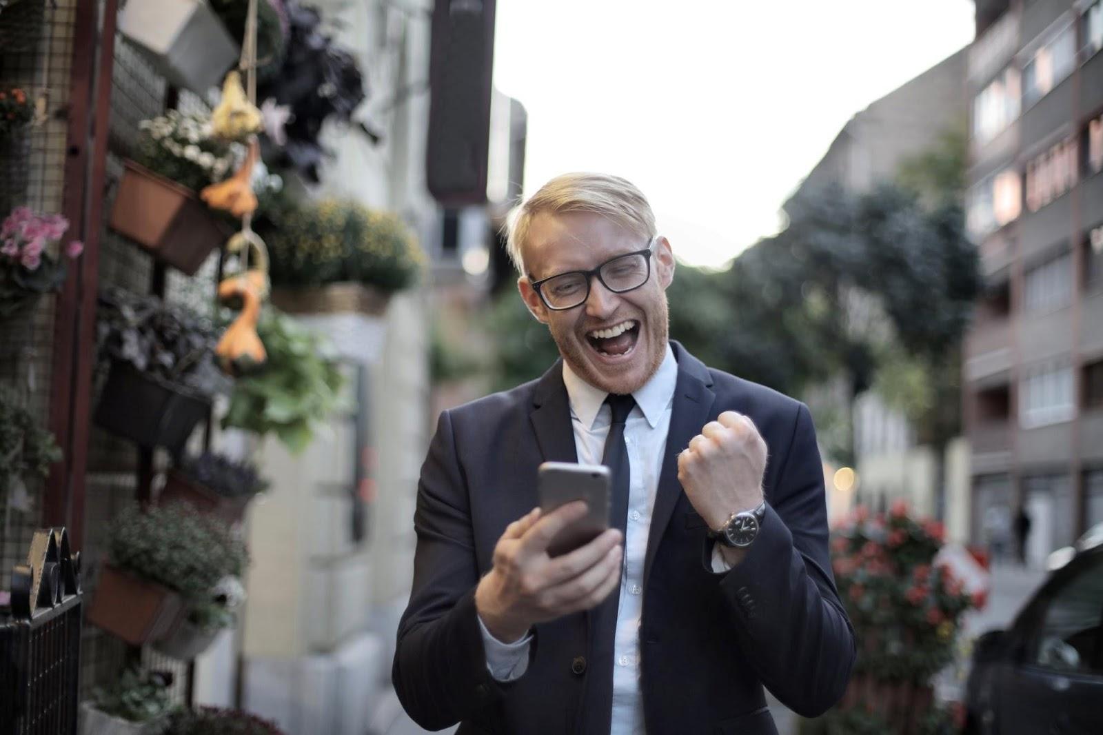 Businessman celebrating after receiving message on smartphone