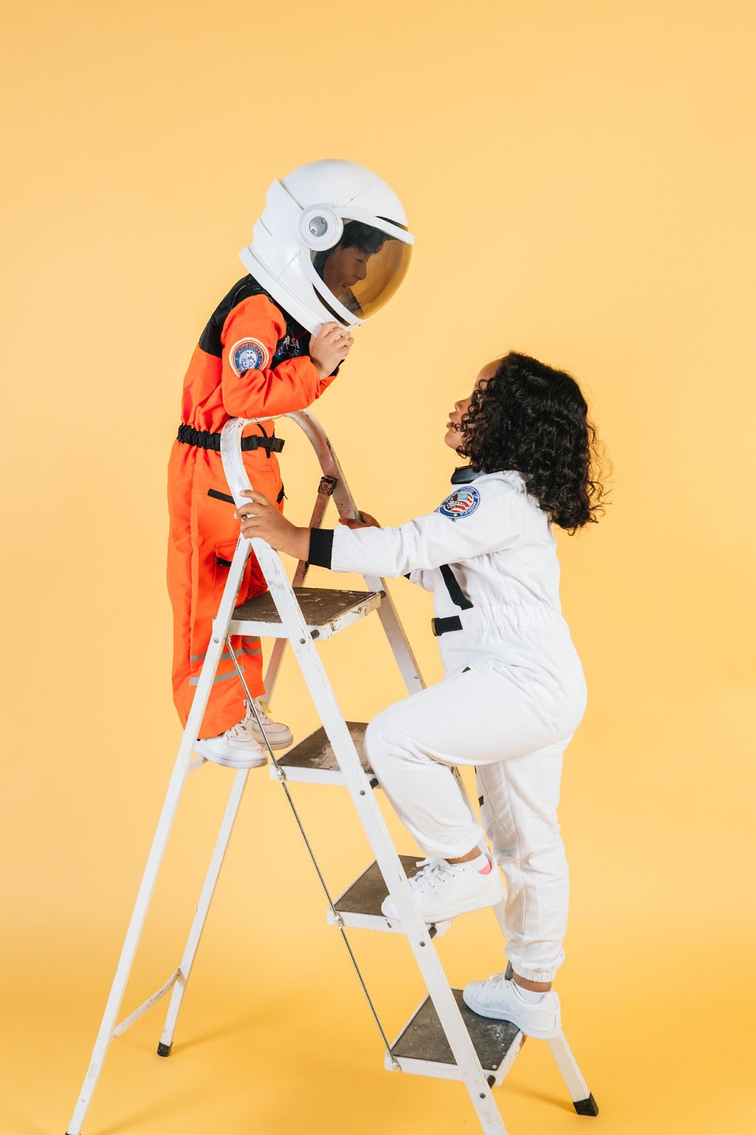 Two children in space suits climbing a white ladder