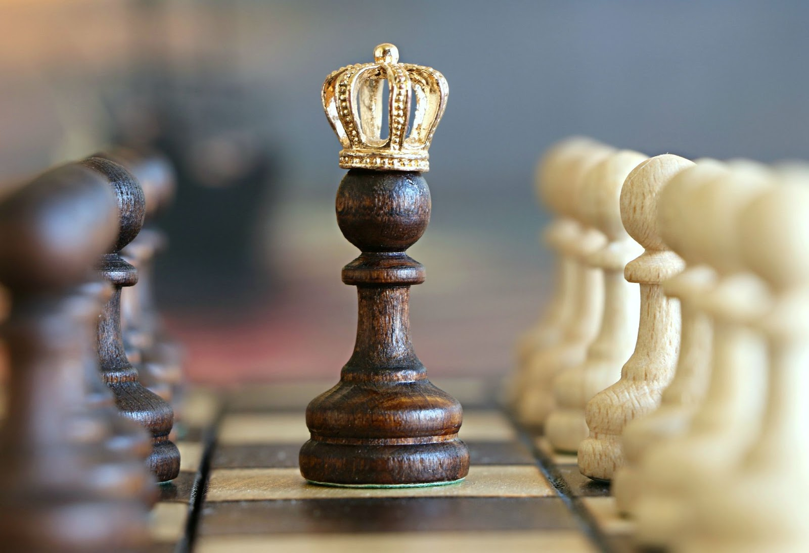 Black chess piece with gold crown on top