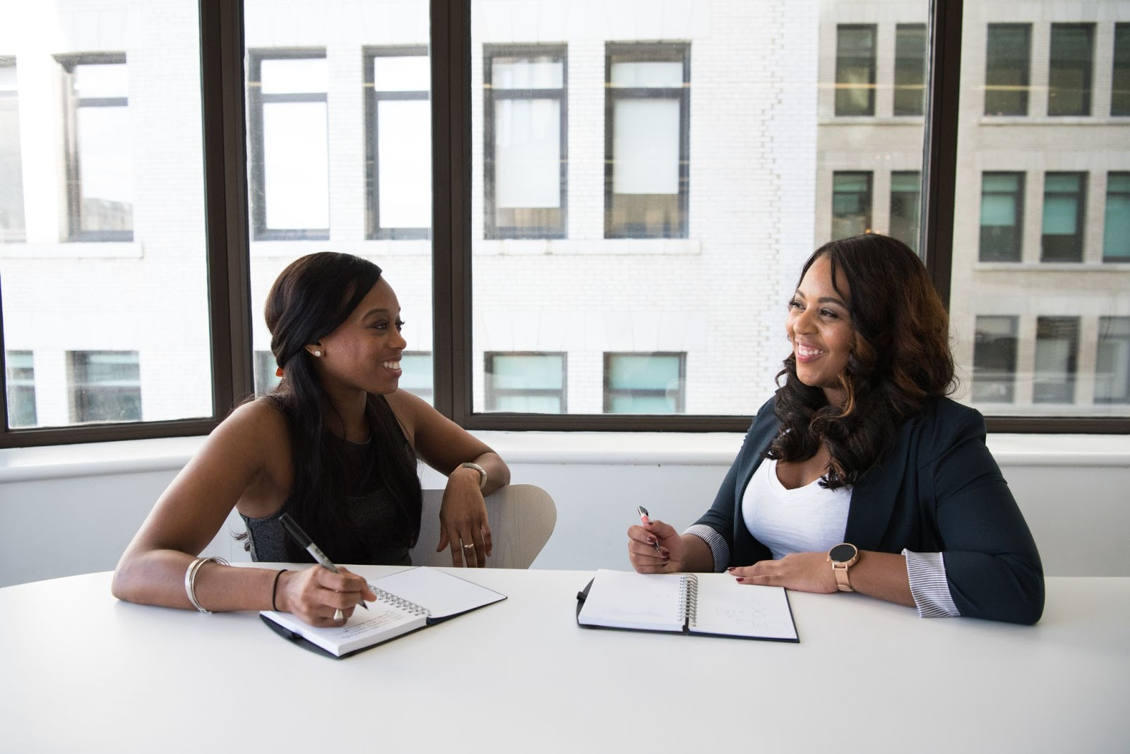 Two women smiling and working at desk
