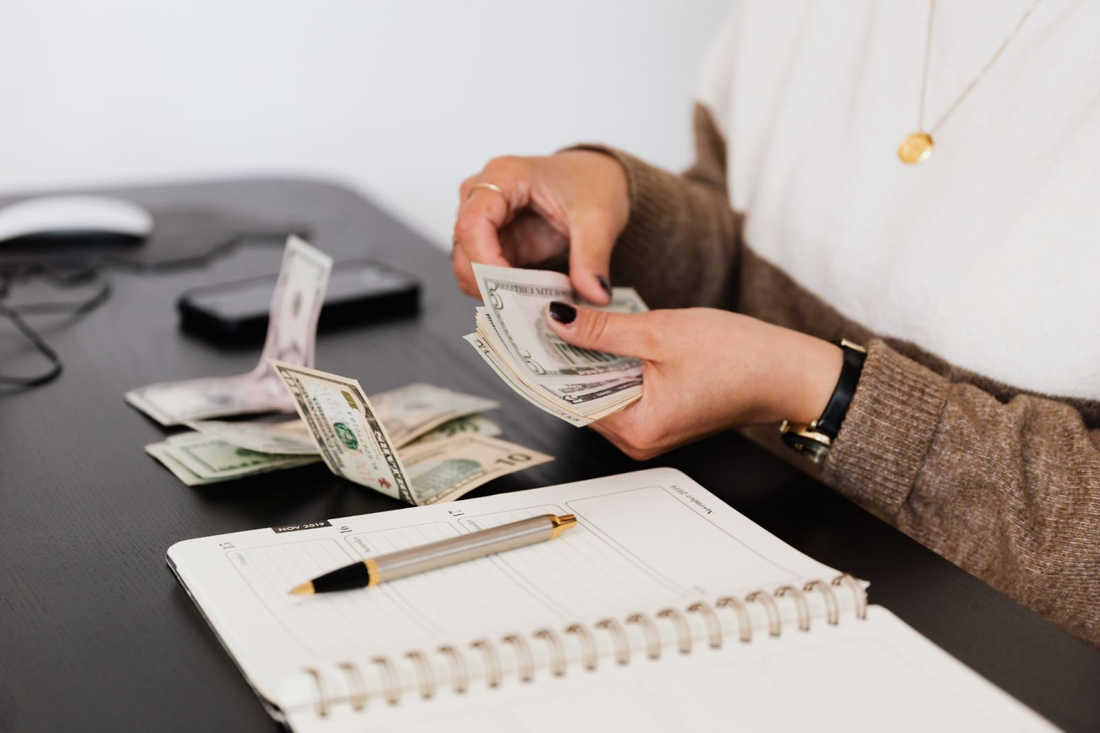 Woman in white and brown jumper counting dollar bills