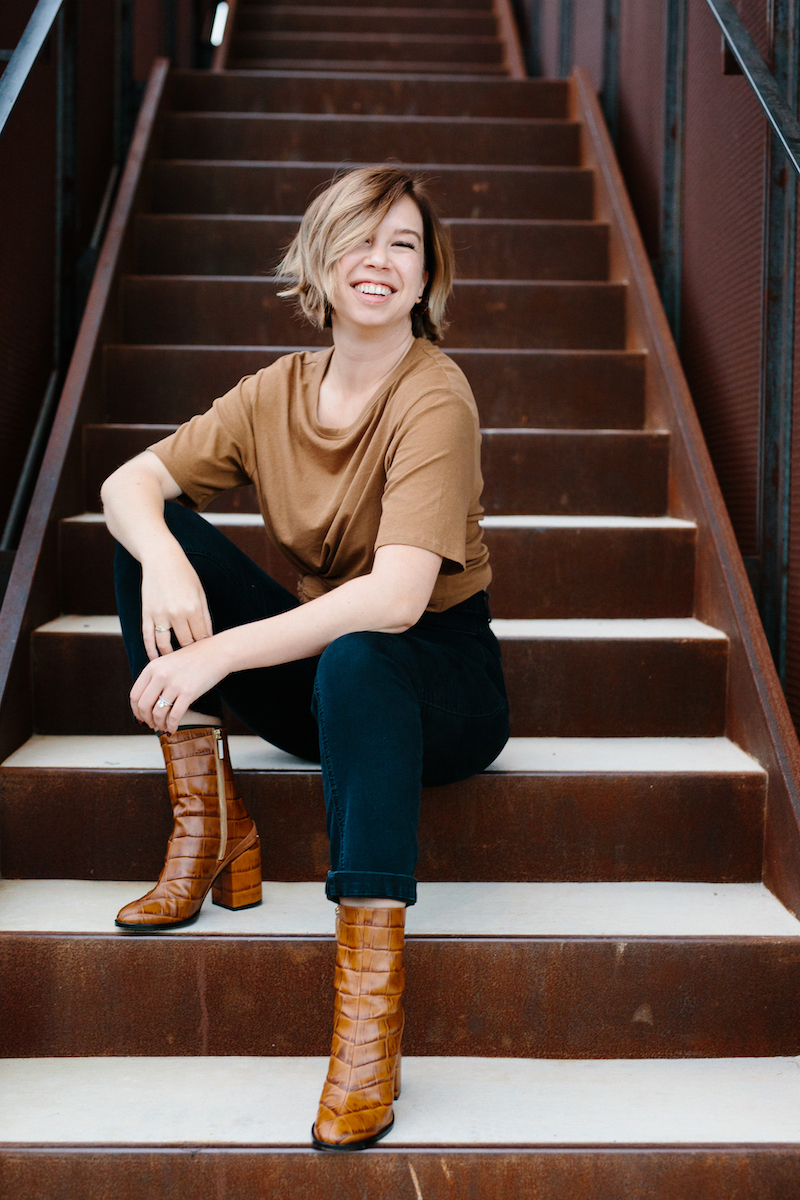 photo of Elyse in a brown t-shirt and black jeans, sitting on rust colored metal steps, laughing