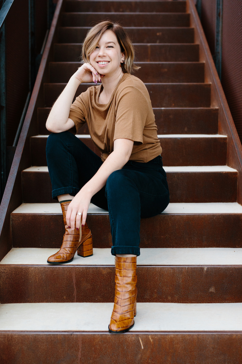 photo of Elyse in a brown t-shirt and black jeans, sitting on rust colored metal steps, smiling at you
