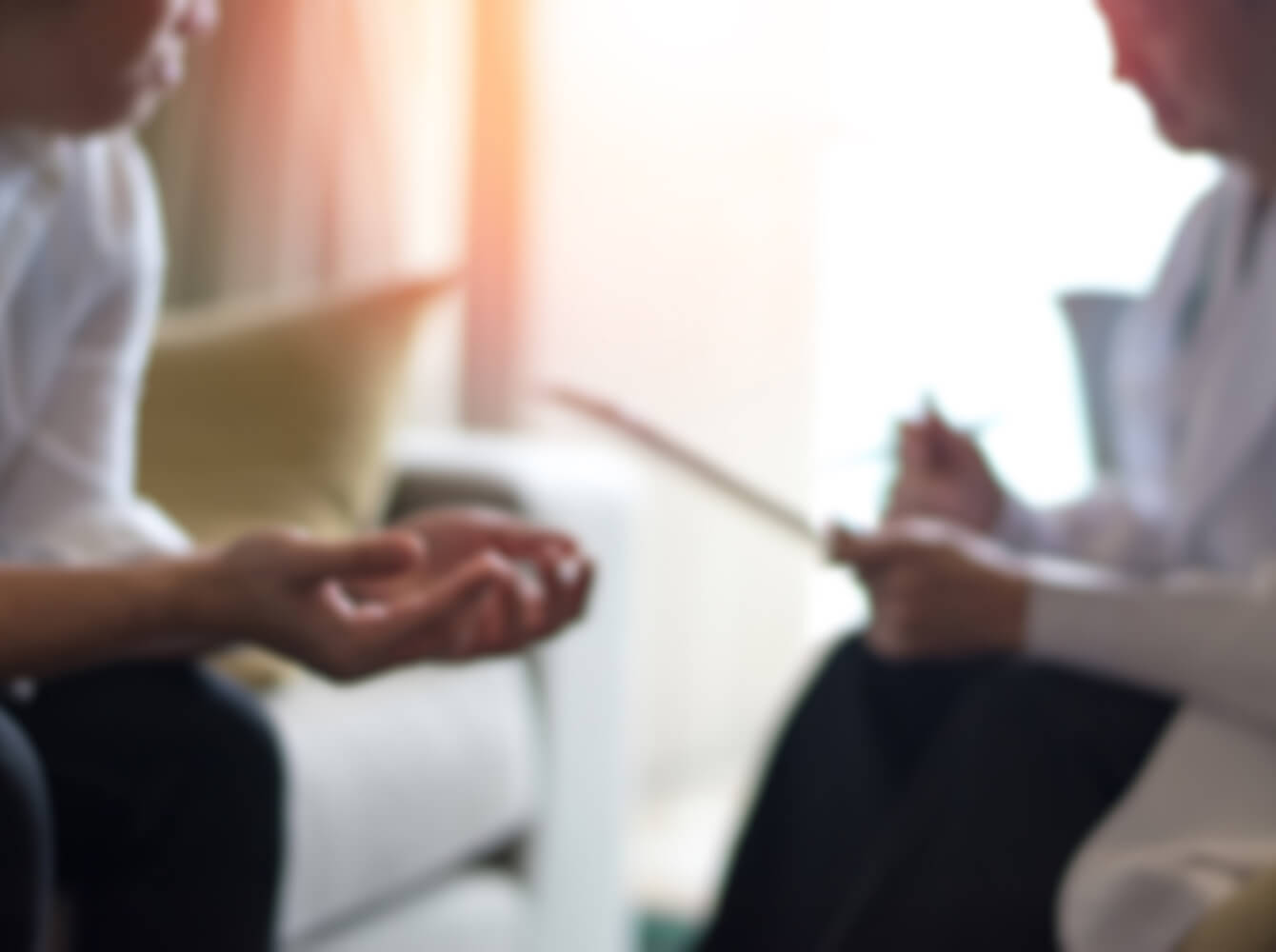 Image of two people out-of-focus in a counseling session