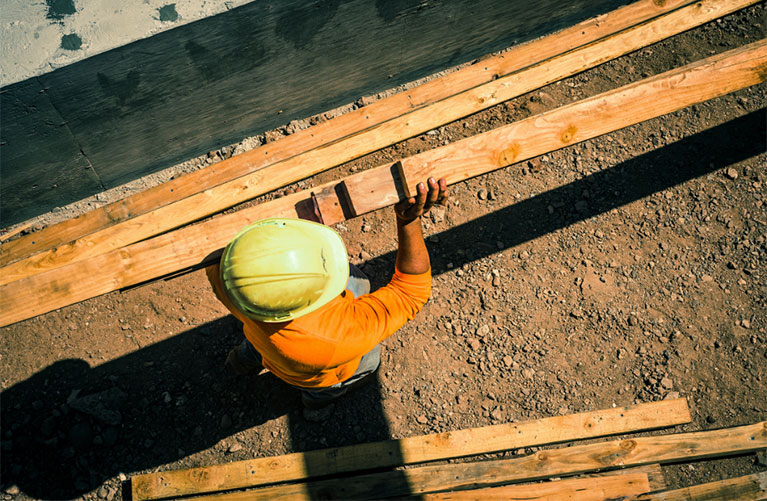 A construction worker carrying lumber. View from above.