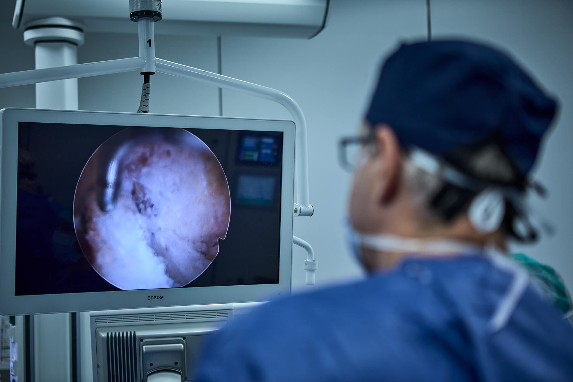Portrait of Dr. Ioan Dunca looking at the monitor while performing arthroscopy