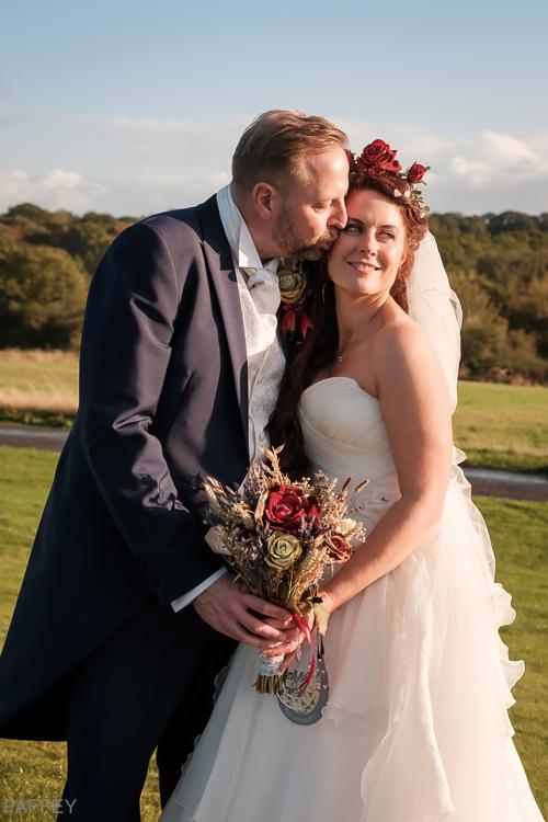 groom kissing bride on her cheek