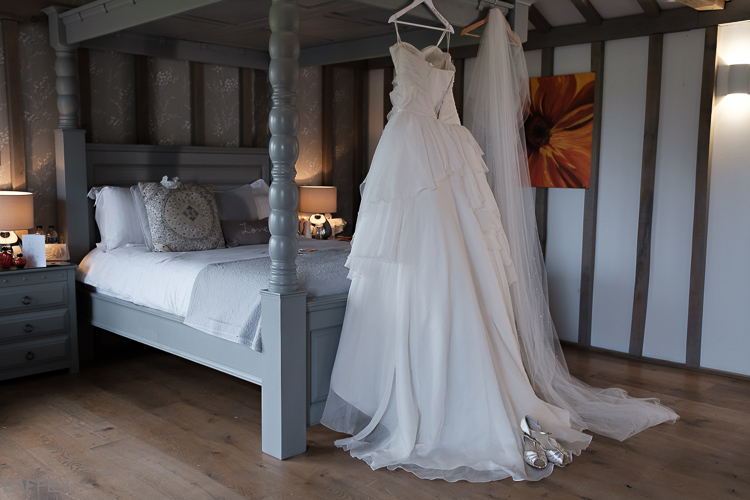 wedding dress hanging from a four poster bed